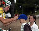 (Click for larger image) The series leader Mark Renshaw signs an autograph for a fan in the Botanical Gardens  after stage four.